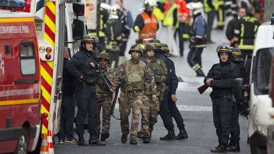 French soldiers and police work during a raid in Paris Nov. 18.