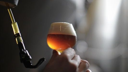 A beer sample is tested at Mount Carmel Brewing Company
