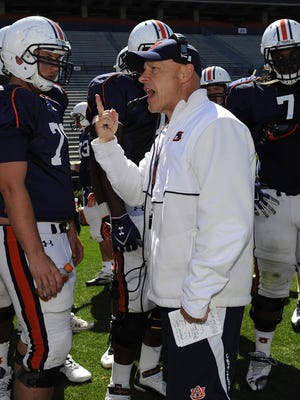 Auburn offensive line coach J.B. Grimes emphasizes a point to his players at practice in this 2013 file photo. Grimes returned to his duties Friday after a surgical procedure.
