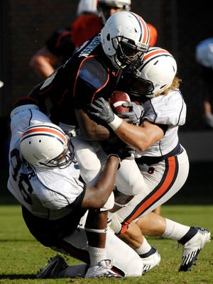 Running back Jovon Robinson is tackled by defenders Devaunte Sigler and Jake Holland Monday. Auburn football practice, first day in pads on Monday, Aug. 6, 2012 in Auburn, Ala. Todd Van Emst