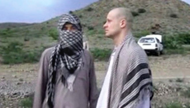 In this image taken from video obtained from Voice Of Jihad Website, Sgt. Bowe Bergdahl, stands with a Taliban fighter in eastern Afghanistan. The video purportedly shows the handover of Bergdahl from the Taliban to U.S. forces.