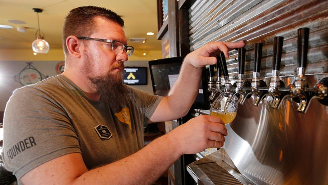 Curator Mike Vanaman draws a glass of Walking Ashland, a cream ale, Friday, March 2, 2018, at Brokerage Brewing Company, 2516 Covington Street in West Lafayette.
