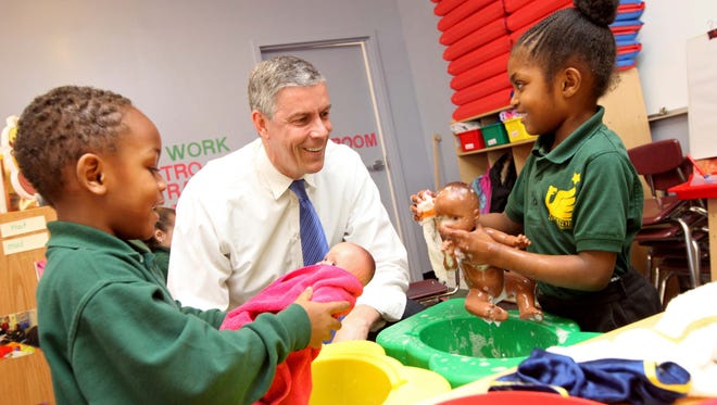 U.S. Education Secretary Arne Duncan visits with pre-kindergarteners Zion Edwards (left) and Carmah McRae at EastSide Charter School Wednesday.