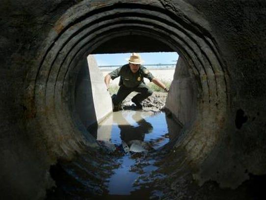 A U.S. Border Patrol agent looks into a storm drain
