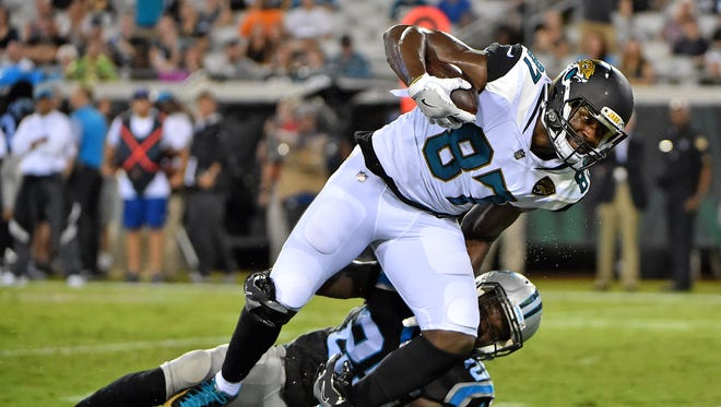 Carolina Panthers defensive back Damian Parms (25) brings down Jacksonville Jaguars tight end Neal Sterling (87) during the second half at EverBank Field.