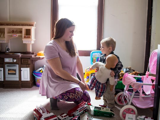 Jaxson Howard, 2, plays with his mother, Courtney Albaugh,