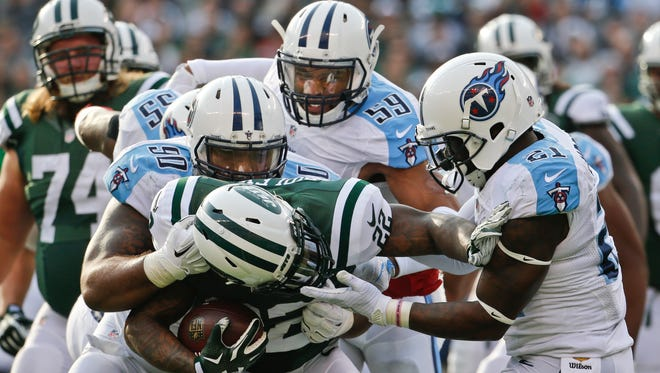 New York Jets' Stevan Ridley (22) is tackled by Tennessee Titans' Da'Norris Searcy (21) and DaQuan Jones (90) during the first half.