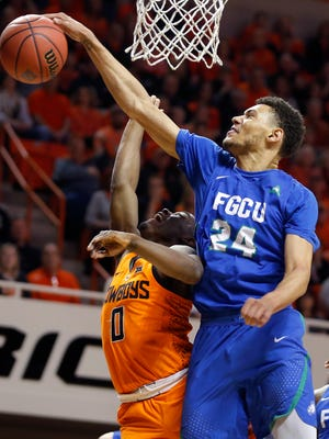 Florida Gulf Coast's Michael Gilmore (24) blocks the shot of Oklahoma State's Brandon Averette (0) during a first-round NIT tournament game Tuesday in Stillwater, Okla. (Bryan Terry/The Oklahoman via AP)