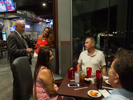Stuart Ed, Las Cruces city manager, standing, checks for the results of the GO Bond election, along side Marci Dickerson, who hosted a watch party at the Game II, Tuesday August 21, 2018.
