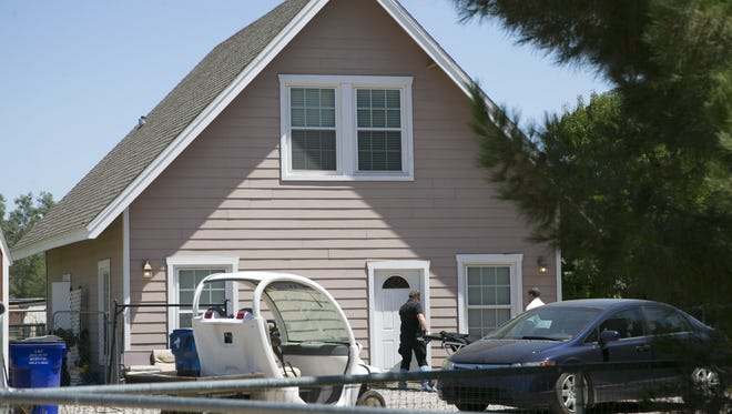 Investigators bring a gurney into the home at the 17700 block of East Prescott Place of unincorporated Maricopa County near south Gilbert where multiple bodies were found on Tuesday, July 26, 2016.