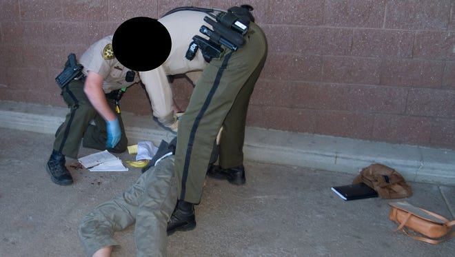 Deputies restrain Jared Loughner after the 2011 shooting of then-U.S. Rep. Gabby Giffords at a Safeway near Tucson. Photo redactions made by the FBI.