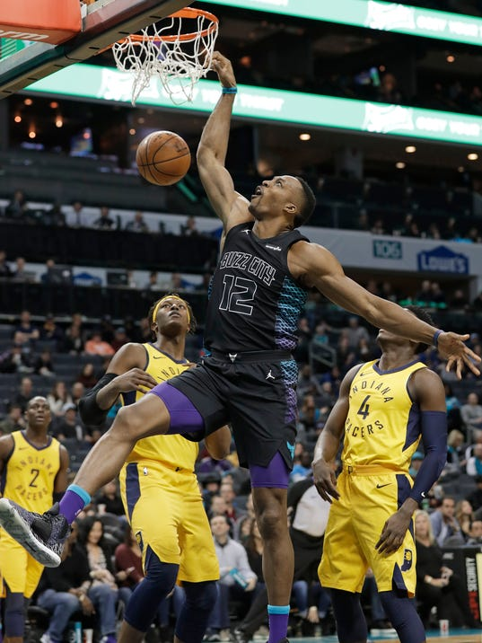 Charlotte Hornets' Dwight Howard, center, dunks in front of Indiana Pacers' Myles Turner, left, and Victor Oladipo, right, during the first half of an NBA basketball game in Charlotte, N.C., Friday, Feb. 2, 2018. (AP Photo/Chuck Burton)