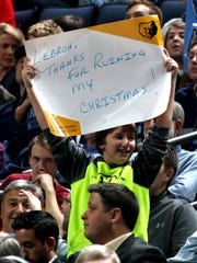 A young basketball fan holds a sign directed at LeBron