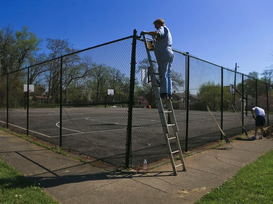 Volunteer Dave Ruhl paints a fence at Ballard Park in Louisville's Smoketown neighborhood as part of the Brightside Community-wide Cleanup that coincided with Give A Day week of service in Louisville.