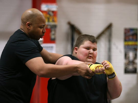 Christopher Rhabb, left, corrects the boxing form of Tyler Rust at Rochester Fight Factory.  Rhabb has offered to help Tyler get more  healthy and control his weight better.