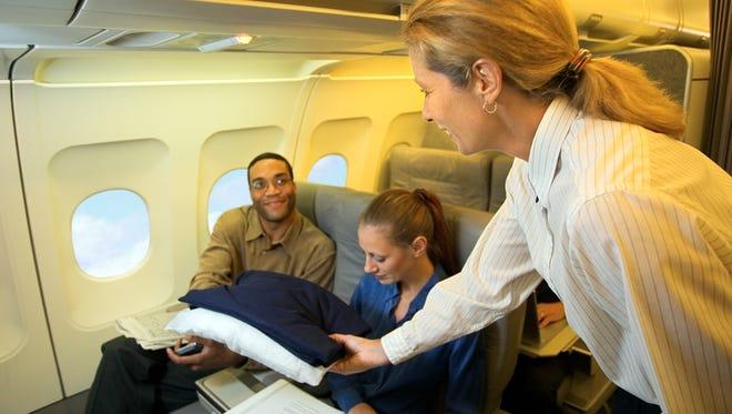 Flight attendant giving a passenger a pillow and blanket.