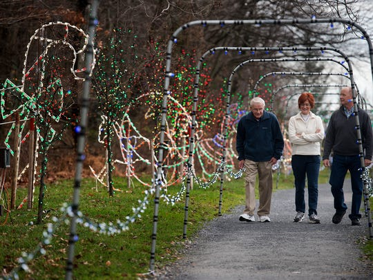 From the left, Ken Gross, of Windsor Township, takes a walk through Christmas Magic in Rocky Ridge Park on Sunday with his daughter, Nancy Lamar, and son-in-law Jesse Lamar, both of Anderson, S.C.
