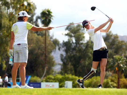 LPGA golfer Juli Inkster holds an alignment stick against the head of high school golfer Sydney Pomajzl, 16, from Wyoming, to help her keep her head still as the teen takes a practice swing on the seventh tee box while playing in the ANA Inspiration Pro-Am Wednesday, March 30, 2016, at Mission Hills Country Club in Rancho Mirage, Calif. Pomajzl was born without most of her right ankle bone and required an amputation as a baby.