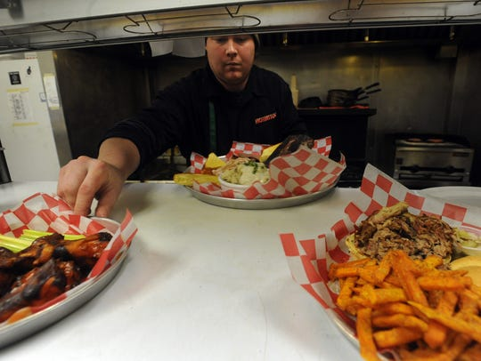 Mo Jeaux's Joey Wilkinson prepares food while working