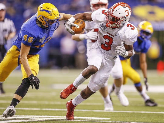 Center Grove Trojans' Russ Yeast (3) takes off on a