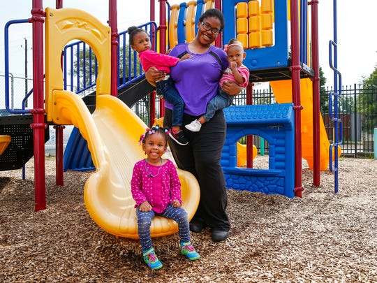 Leilah, 4, Grace, 2, and Olivia, 1, pose for a photo on the playground at Wheeler Mission Center for Women & Children with their mother Adrienne Brown on Wednesday, July 12, 2017.