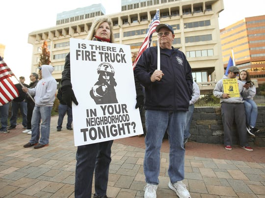 File photo: Susan Wiley and Wilmington Fire union president Kevin Turner gather in November 2016 opposite the Louis L. Redding City County Building to protest the city's decision to resume a payroll savings plan by reducing the number of on-duty firefighters.