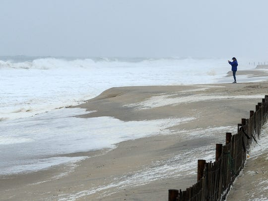 "A visitor braves the winds to take a photos as a strong ""Nor Easter"" storm has brought some wind, rain and beach erosion with minor flooding to Rehoboth Beach and Dewey Beach on Wednesday March 21st. Special to the News Journal / Chuck Snyder"