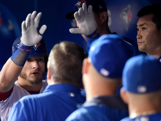 Toronto Blue Jays' Josh Donaldson, left, is congratulated in the dugout by teammates after hitting a solo home run in sixth inning of a baseball action against the Tampa Bay Rays in Toronto on Wednesday, Aug. 16, 2017. (Nathan Denette/The Canadian Press via AP)