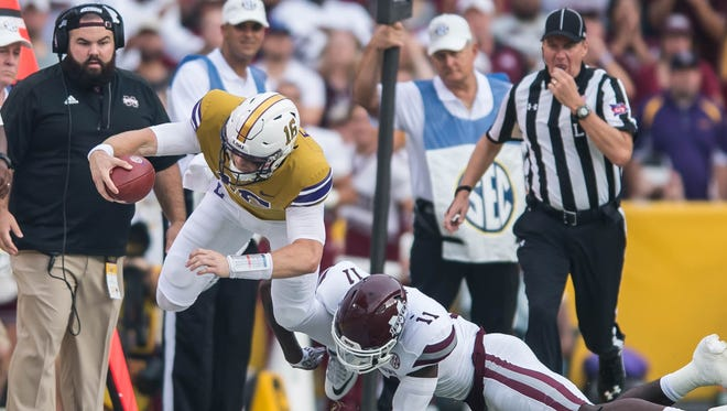 LSU Tigers quarterback Danny Etling (16) leaps forward to get the first down during the first half of a SEC game between Mississippi State and the LSU Tigers in Death Valley on Saturday Sept. 17, 2016.