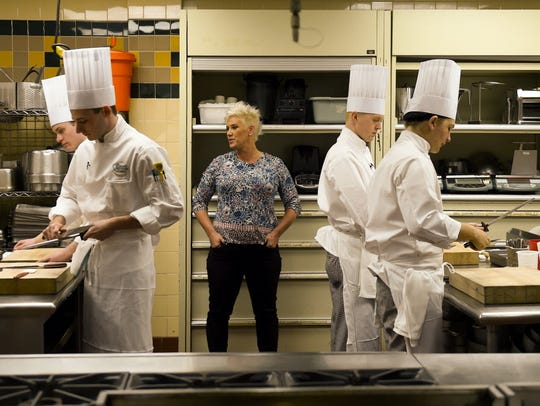 Chef Anne Burrell stands between students Mason Aronson,
