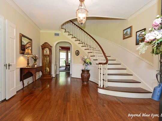A curved staircase is the focal point of the entryway