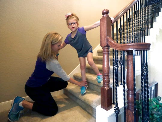 Stacey English, left, teaches her 7-year-old daughter, Addison, how to use the stairs in Houston on Friday, June 23, 2017. Stacey has modest desires for her daughter: Be able to eat without gagging and move both her arms. But since Addison's occupational therapist went out of business this winter, the child with a rare genetic disorder has regressed in her fight to do even that much. (AP Photo/David J. Phillip)