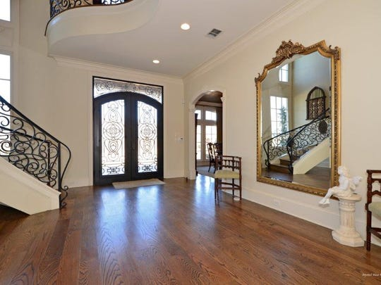 The front doors open to a curved staircase with custom ironwork.