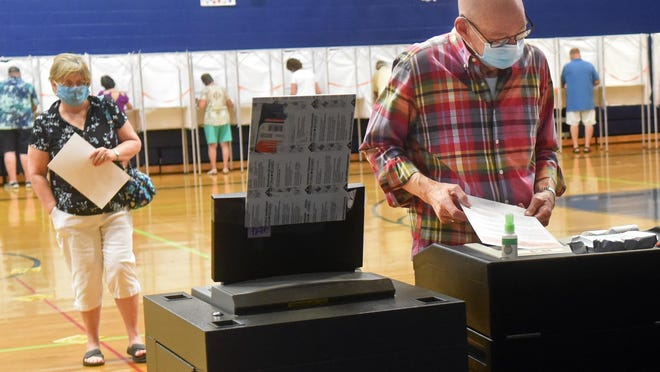 York resident Richard Wagner feeds ballots into the machine July 14, 2020, after casting his decisions on voting day at York High School.