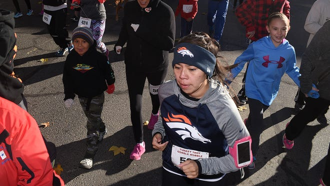 Kelsey Tsosie, of Fruitland, takes off at the start of the Turkey Trot and Gobble Wobble 5K run and 2-mile walk on Saturday in downtown Farmington.