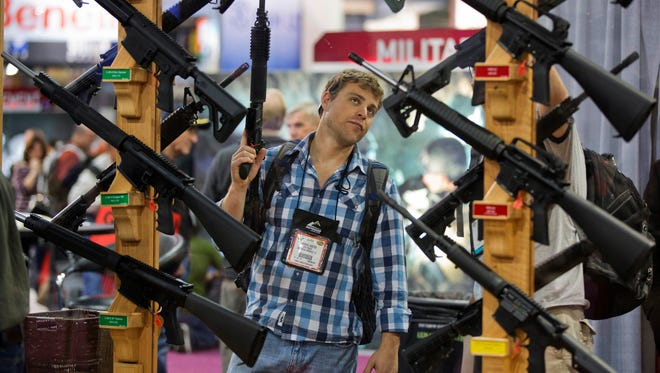 FILE - In this Jan. 17, 2013, file photo, Michael Kiefer, of DeFuniak Springs, Fla., checks out a display of rifles at the Rock River Arms booth during the 35th annual SHOT Show in Las Vegas.