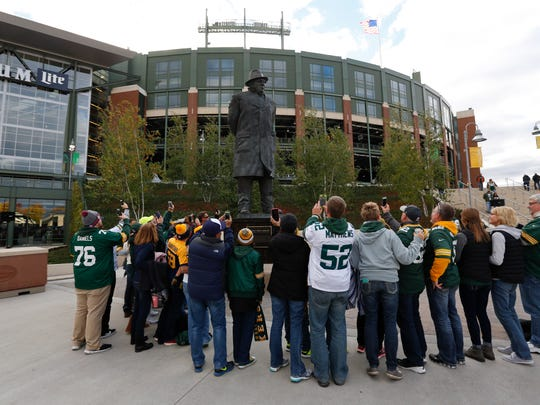 Fans gather around Vince Lombardi statue outside Lambeau Field before an NFL football game between the Green Bay Packers and the Chicago Bears, Thursday, Oct. 20, 2016, in Green Bay, Wis. (AP Photo/Mike Roemer)