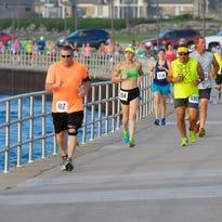 Participants run along Thomas Edison Parkway, Sunday, during the Blue Water Half Marathon.