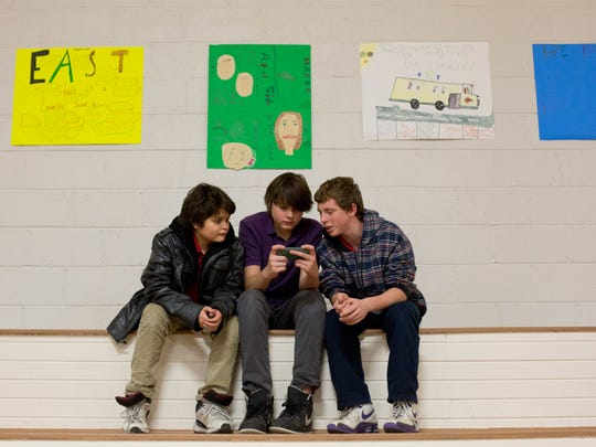Adam Jackson, 11, Mat Jackson, 13, and Alex Gault, 13, all of Port Huron, hang out in the gym during a Winter Wonderland community event Thursday, Dec. 17, 2015 at East Shore Leadership Academy in Port Huron.