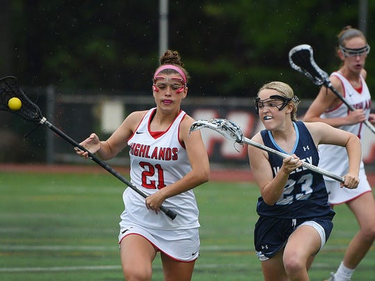 Melina North (no. 21) of Northern Highlands runs with the ball as Kamryn Nevard (no. 23) of  Wayne Valley gives chase in the first half during the North 1, Group 3 girls lacrosse state semifinal game at Northern Highlands High School in Allendale on May 22nd, 2017. Northern Highlands defeated Wayne Valley 14 to 1.