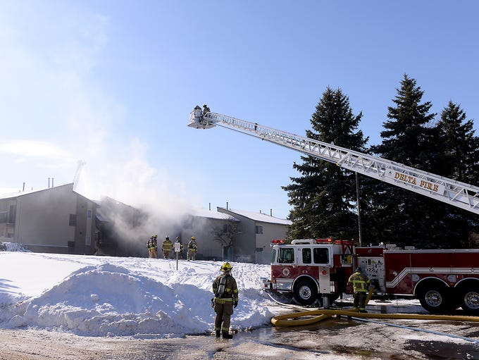 Two ladder trucks work on controlling the fire Thursday,