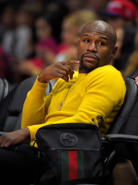 Boxer Floyd Mayweather Jr. watches the Los Angeles Clippers play the Phoenix Suns during the first half of a preseason NBA basketball game, Wednesday, Oct. 22, 2014, in Los Angeles. (AP Photo/Mark J. Terrill)