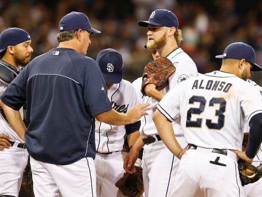 San Diego Padres pitching coach Darren Balsley, second from left, talks with starter Andrew Cashner after Cashner loaded the bases with a walk and just before before he surrendered a two-run single to the Arizona Diamondbacks during the third inning of a baseball game on Friday, May 2, 2014, in San Diego.  (AP Photo/Lenny Ignelzi)