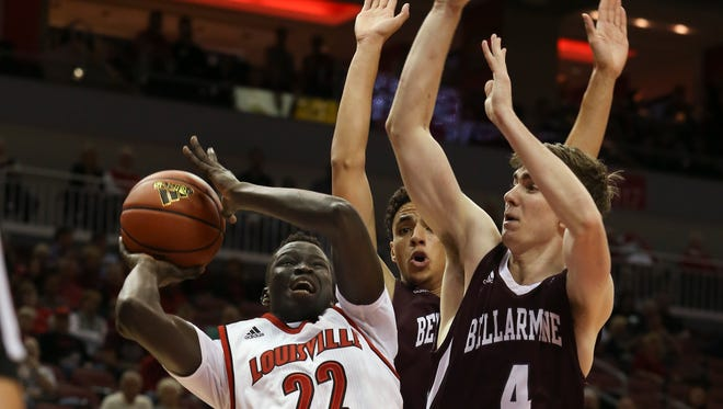 U of L's Deng Adel, #22, tries to adjust his shot while being hounded by Bellarmine's Tyler Landry, #42, and George Suggs, #4, during their game at the KFC Yum! Center.Nov. 1, 2015