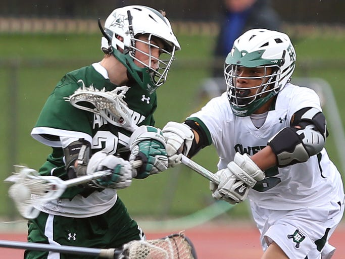 Archmere's Ben Revak (left) shoots and scores past Tower Hill's  Noah Thomas in the second period of the Hillers' 6-5 win Tuesday, April 29, 2014.