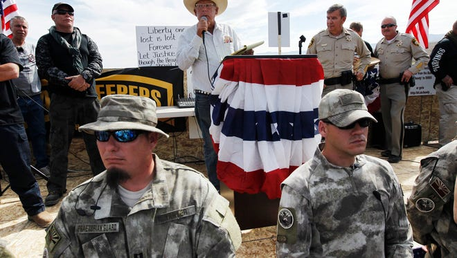 In this April 12, 2014 file photo, rancher Cliven Bundy, center, addresses his supporters along side Clark County Sheriff Doug Gillespie, right, while being guarded by self-described militia members in the foreground.