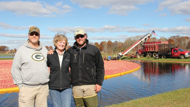 Roy Diver, NRCS District Conservationist (left) Mary Brazeau Brown (center), Glacial Lake Cranberries (GLC) President; and Stephen Brown,  GLC Vice President, oversee cranberry harvesting at GLC.