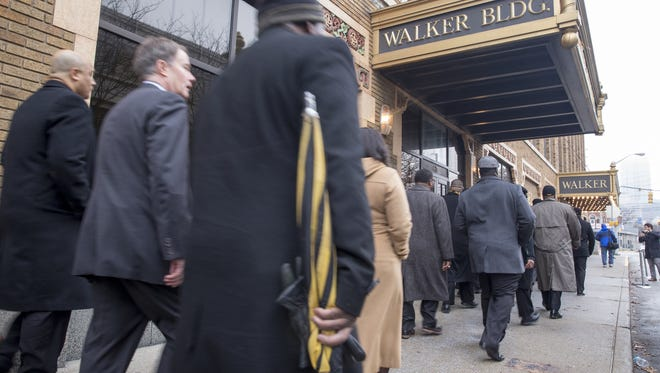 A procession of about 150 people head toward the annual MLK Jr. event at Madame Walker Theatre, Monday, January 16, 2018.