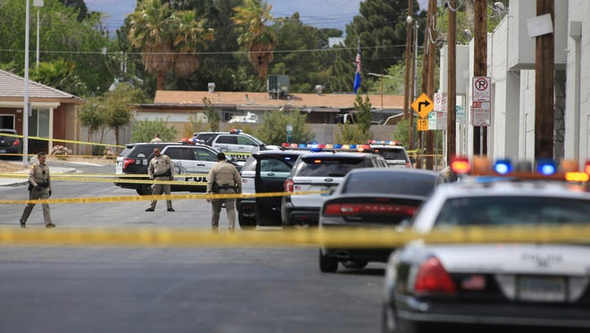 Las Vegas police investigate an officer-involved shooting in Las Vegas on Friday, March 31, 2017. Police in Las Vegas say a man who was shot at least twice by an officer responding to a call about an armed man at a business is in surgery at a hospital. Capt. Kelly McMahill says an officer found the man on the ground behind the business a little after 12:30 p.m. Friday, and shot him when he sat up with the gun and wouldn't put it down. (Brett Le Blanc/Las Vegas Review-Journal via AP)