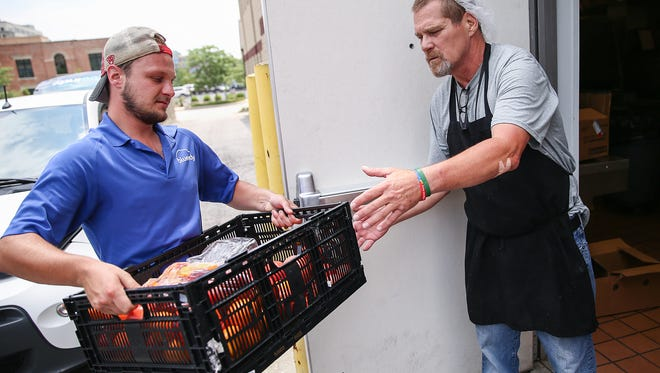 """From left, BlueIndy marketing ambassador Daniel Wilburn hands fresh produce donations off to Dieter Brumfield at Wheeler Mission's men's shelter, Indianapolis, Wednesday, July 19, 2017. The Original Farmer's Market at City Market downtown encourages customers to purchase an item to contribute to the weekly collection in a program called """"Buy 2, Give 1."""" Vendors participate as well and the produce donations are taken by BlueIndy to a local shelter or food pantry after the market every Wednesday."""